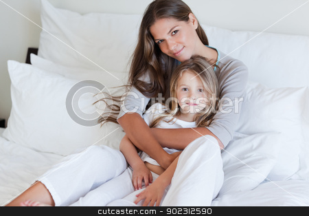 Young mother and her daughter posing on a bed stock photo, Young mother and her daughter posing on a bed while looking at the camera by Wavebreak Media