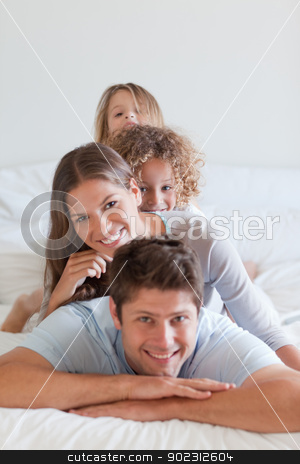 Portrait of a family lying on each other stock photo, Portrait of a family lying on each other in a bedroom by Wavebreak Media