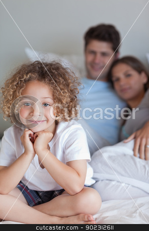 Portrait of a boy sitting on his parents's bed stock photo, Portrait of a boy sitting on his parents's bed while looking at the camera by Wavebreak Media