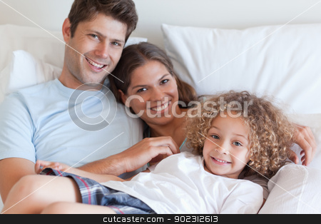 Smiling family relaxing on a bed stock photo, Smiling family relaxing on a bed while looking at the camera by Wavebreak Media