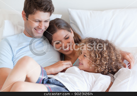 Happy family relaxing on a bed stock photo, Happy family relaxing on a bed while looking at each other by Wavebreak Media