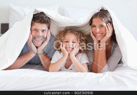 Happy family posing under a duvet stock photo, Happy family posing under a duvet while looking at the camera by Wavebreak Media