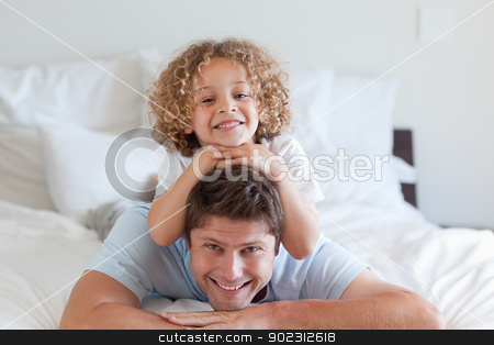 Child lying on fathers back stock photo, Child lying on fathers back in bed by Wavebreak Media