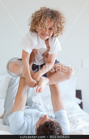 Father lifting child on bed stock photo, Father lifting smiling child on bed by Wavebreak Media