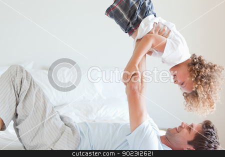 Side view of father lifting child on bed stock photo, Side view of father lifting smiling child on bed by Wavebreak Media