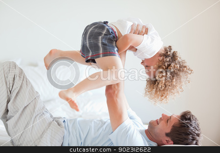 Side view of smiling father lifting child stock photo, Side view of smiling father lifting his child by Wavebreak Media