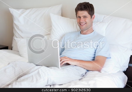 Smiling man lying in bed with laptop stock photo, Smiling man lying in bed with his laptop by Wavebreak Media