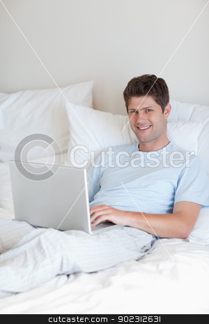 Smiling man lying in bed with notebook stock photo, Smiling man lying in bed with his notebook by Wavebreak Media