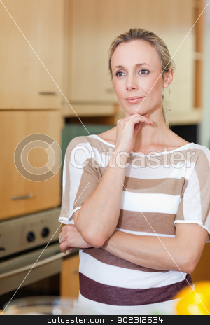 Woman in thoughts standing in kitchen stock photo, Woman in thoughts standing in the kitchen by Wavebreak Media