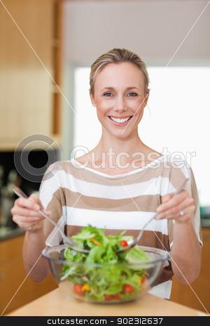 Smiling woman stirring salad stock photo, Smiling woman stirring her salad by Wavebreak Media
