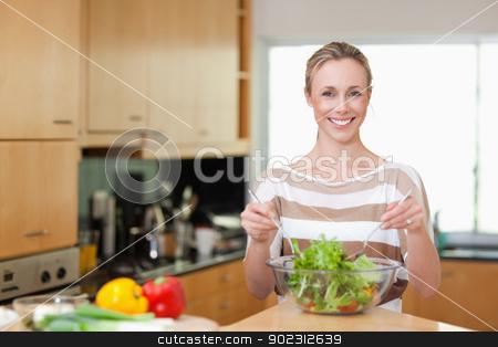 Woman preparing healthy salad stock photo, Smiling woman preparing healthy salad by Wavebreak Media