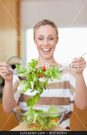 Salad being stirred by woman stock photo, Salad being stirred by smiling woman by Wavebreak Media
