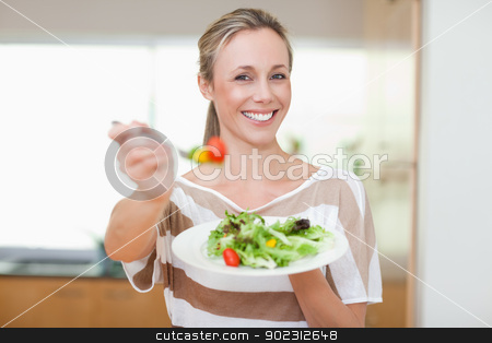 Woman offering healthy salad stock photo, Smiling woman offering healthy salad by Wavebreak Media