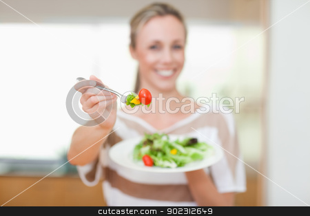 Tomato being offered by woman stock photo, Tomato being offered by smiling woman by Wavebreak Media