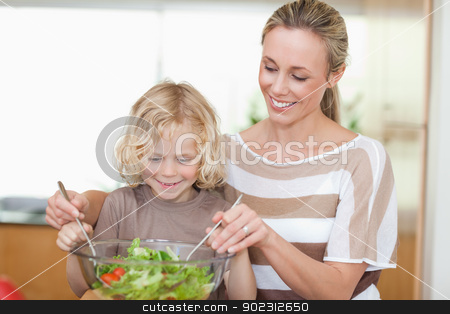 Mother and son preparing salad stock photo, Mother and son preparing salad together by Wavebreak Media