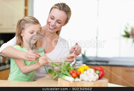 Mother and daughter stirring salad stock photo, Mother and daughter stirring salad together by Wavebreak Media