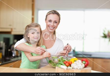 Smiling mother and daughter stirring salad stock photo, Smiling mother and daughter stirring salad together by Wavebreak Media
