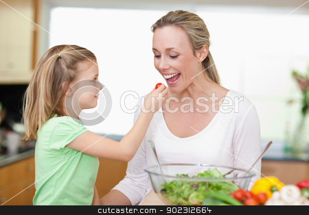 Girl feeding her mother with tomato stock photo, Little girl feeding her mother with tomato by Wavebreak Media