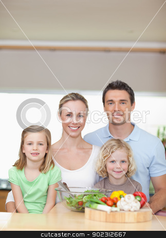 Family standing behind kitchen counter stock photo, Family standing together behind kitchen counter by Wavebreak Media