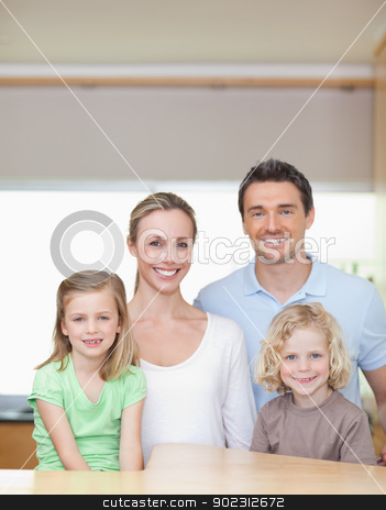 Cheerful family standing in the kitchen together stock photo, Cheerful smiling family standing in the kitchen together by Wavebreak Media