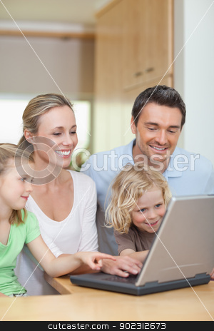 Family using laptop in the kitchen stock photo, Family using laptop in the kitchen together by Wavebreak Media