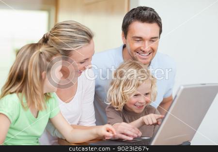 Family using notebook in the kitchen stock photo, Family using notebook in the kitchen together by Wavebreak Media