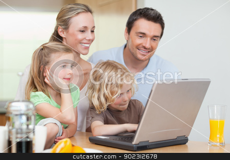 Family using the internet in the kitchen stock photo, Family using the internet in the kitchen together by Wavebreak Media