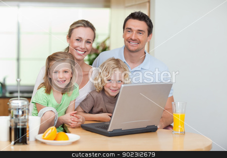 Smiling family using the internet in the kitchen stock photo, Smiling family using the internet together in the kitchen by Wavebreak Media
