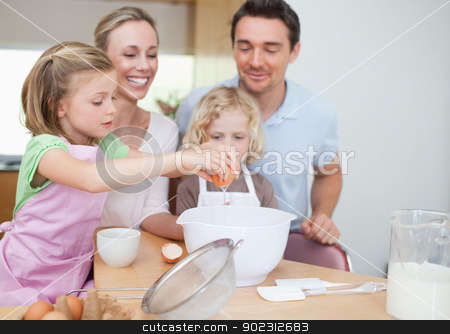 Happy family preparing dough together stock photo, Happy smiling family preparing dough together by Wavebreak Media