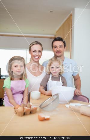 Happy smiling family preparing cookies stock photo, Happy smiling family preparing cookies together by Wavebreak Media