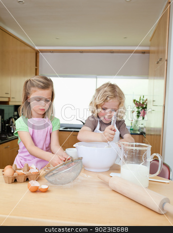 Brother and sister preparing dough stock photo, Brother and sister preparing dough together by Wavebreak Media
