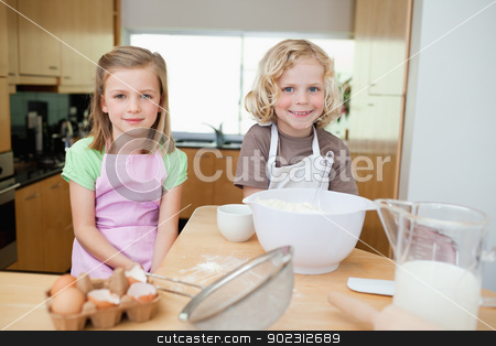 Smiling siblings preparing dough stock photo, Smiling siblings preparing dough together by Wavebreak Media