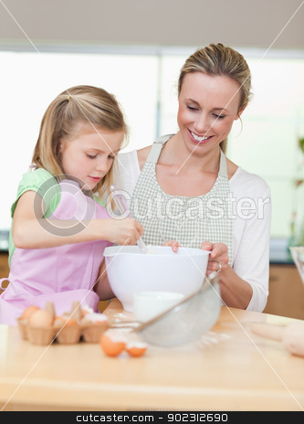 Smiling mother and daughter preparing dough for cookies stock photo, Smiling mother and daughter preparing dough for cookies togehter by Wavebreak Media
