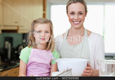 Mother and daughter with bowl in the kitchen stock photo, Mother and daughter together with bowl in the kitchen by Wavebreak Media