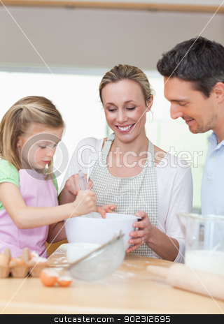 Family preparing cookies together stock photo, Smiling family preparing cookies together by Wavebreak Media