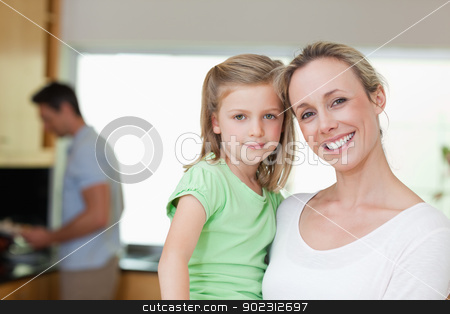 Mother and daughter with father in the background stock photo, Mother and daughter together with father in the background by Wavebreak Media