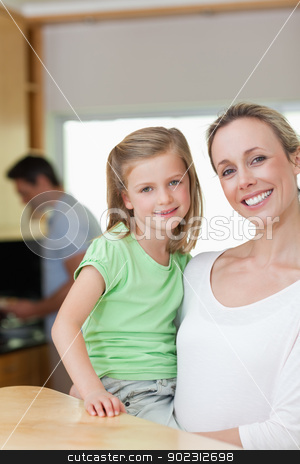 Mother holding her daughter with father in the background stock photo, Smiling mother holding her daughter with father in the background by Wavebreak Media