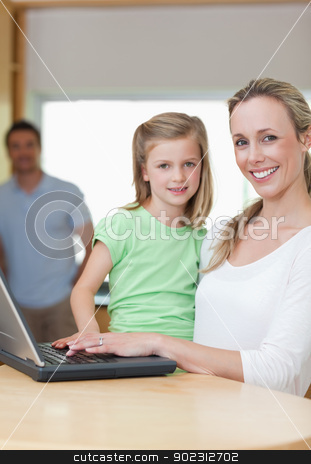 Mother and daughter using notebook with father in the background stock photo, Mother and daughter using notebook together with father in the background by Wavebreak Media