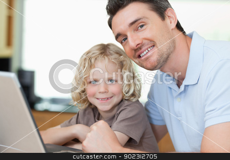 Smiling father and son with notebook stock photo, Smiling father and son together with notebook by Wavebreak Media