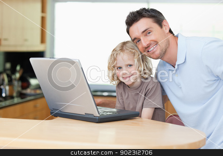 Father and son with notebook in the kitchen stock photo, Father and son together with notebook in the kitchen by Wavebreak Media
