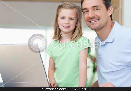Father and daughter together with laptop stock photo, Smiling father and daughter together with laptop by Wavebreak Media