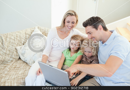 Family on the couch with laptop stock photo, Family together on the couch with laptop by Wavebreak Media