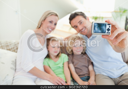 Father taking family picture on couch stock photo, Father taking family picture on the couch by Wavebreak Media
