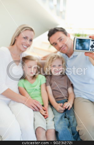 Man taking family picture on sofa stock photo, Man taking family picture on the sofa by Wavebreak Media