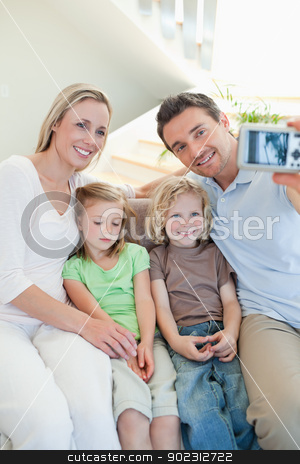 Man taking family picture on couch stock photo, Man taking family picture on the couch by Wavebreak Media