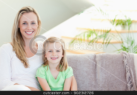 Mother and daughter sitting on couch together stock photo, Mother and daughter sitting on the couch together by Wavebreak Media