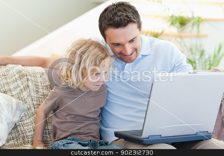 Father and son with laptop on the sofa stock photo, Father and son together with laptop on the sofa by Wavebreak Media