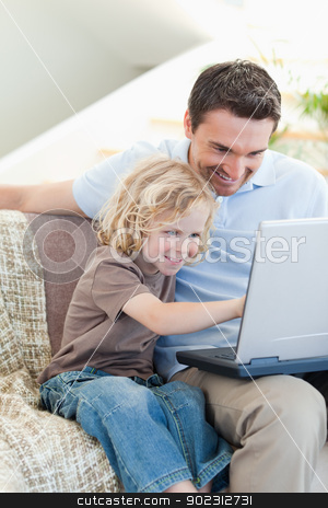 Father and son with notebook on sofa stock photo, Father and son together with notebook on sofa by Wavebreak Media