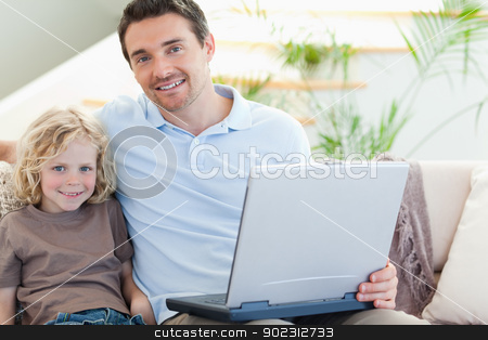 Father and son on couch with laptop stock photo, Father and son together on couch with laptop by Wavebreak Media