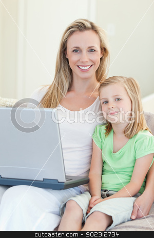 Mother and daughter with laptop on sofa stock photo, Mother and daughter together with laptop on sofa by Wavebreak Media